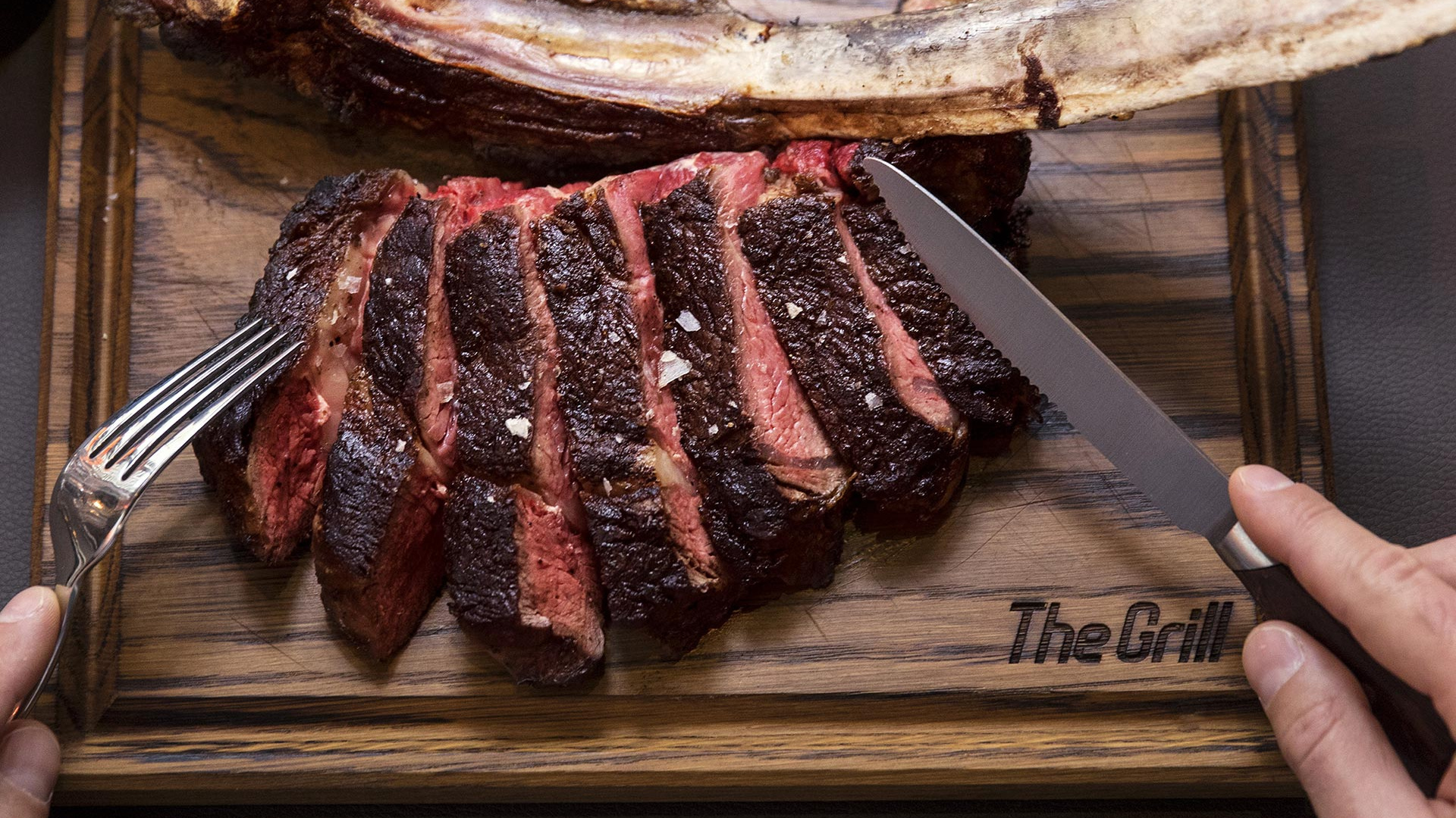 The Grill at McQueen medium rare tomahawk steak off the bone to share between two