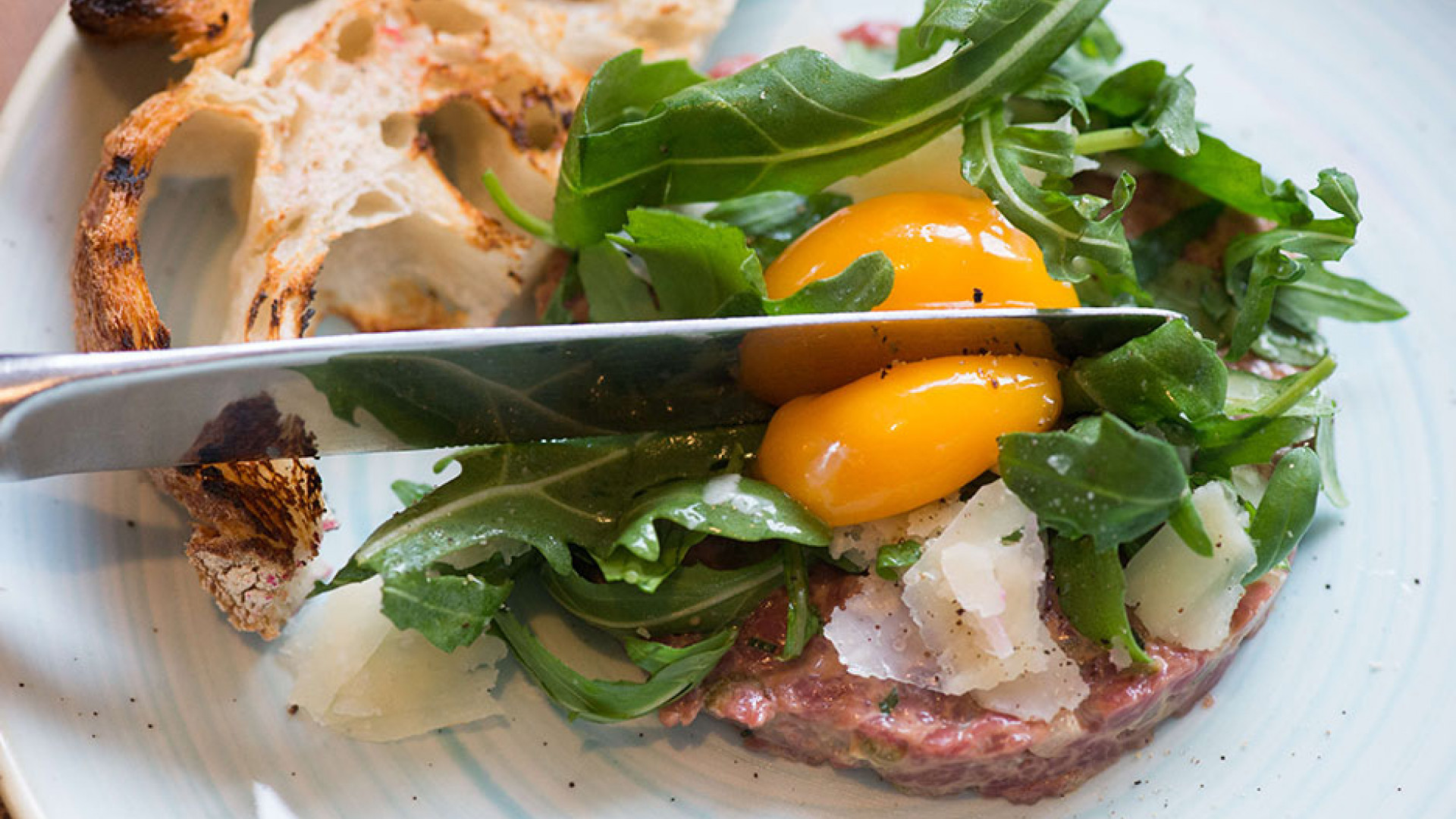 Steak tartare with egg yolk, rocket and sourdough