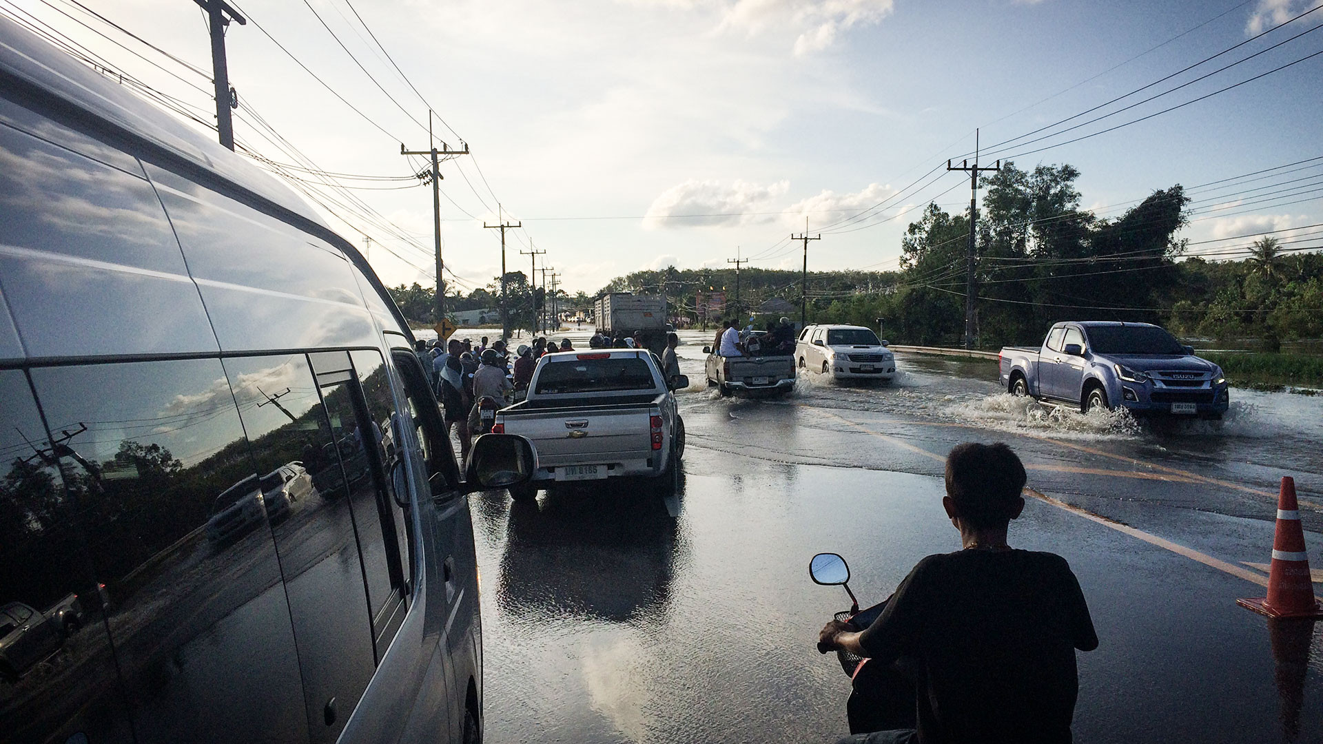 People navigate a flooded road in Trang, southern Thailand