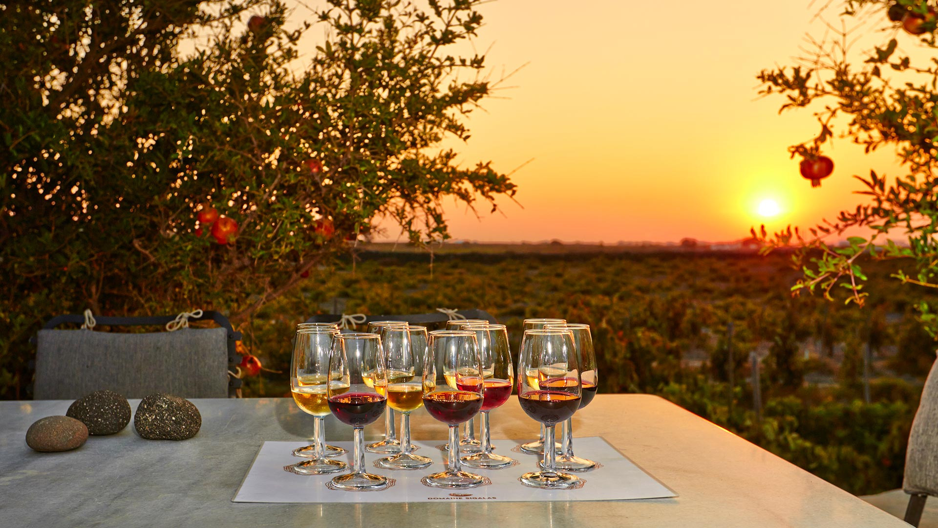 Glasses of volcanic wine on a table with the sun setting in the background over Santorini's vineyards