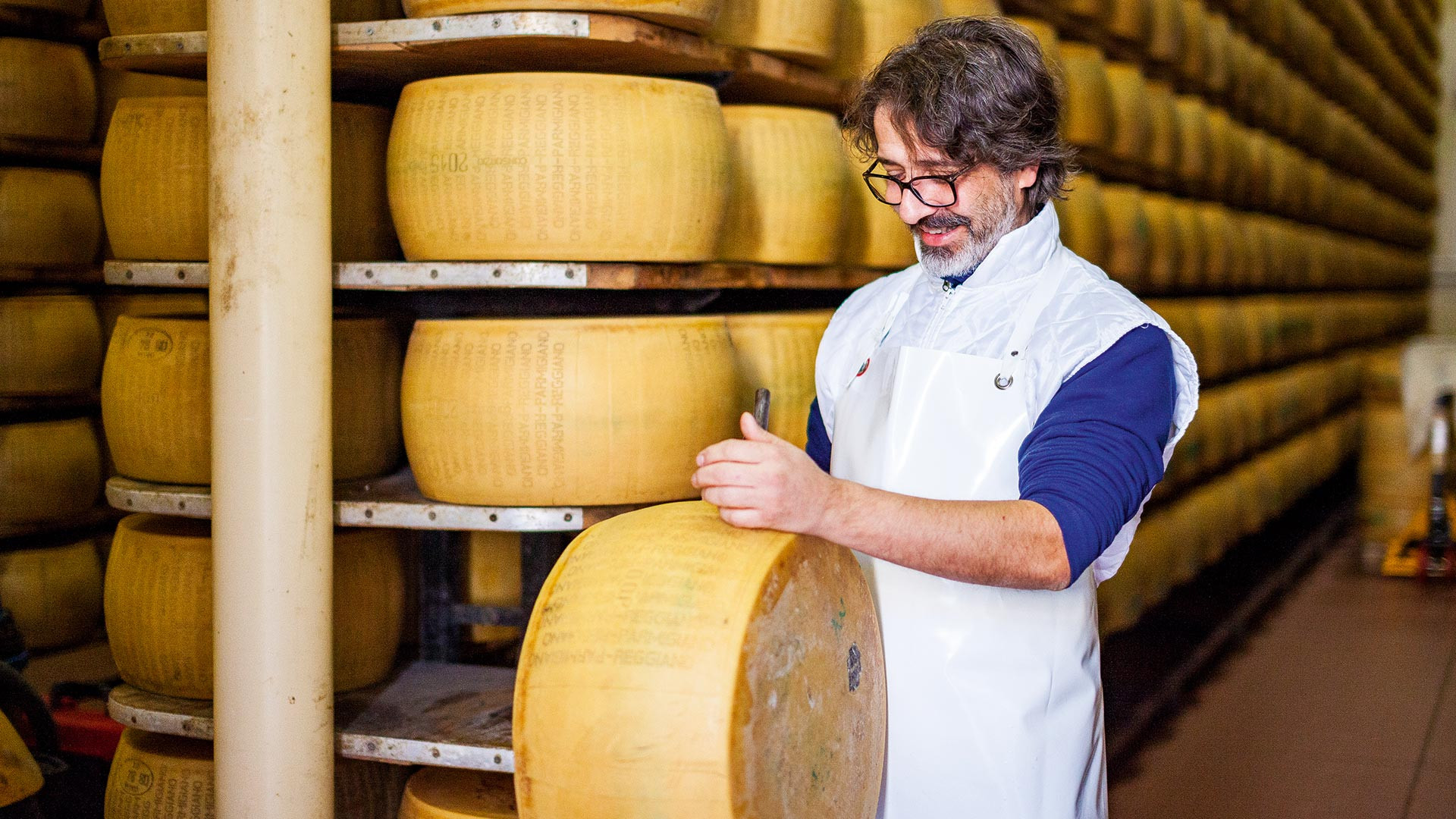 Damiano Delfante inspects one of his wheels of parmesan