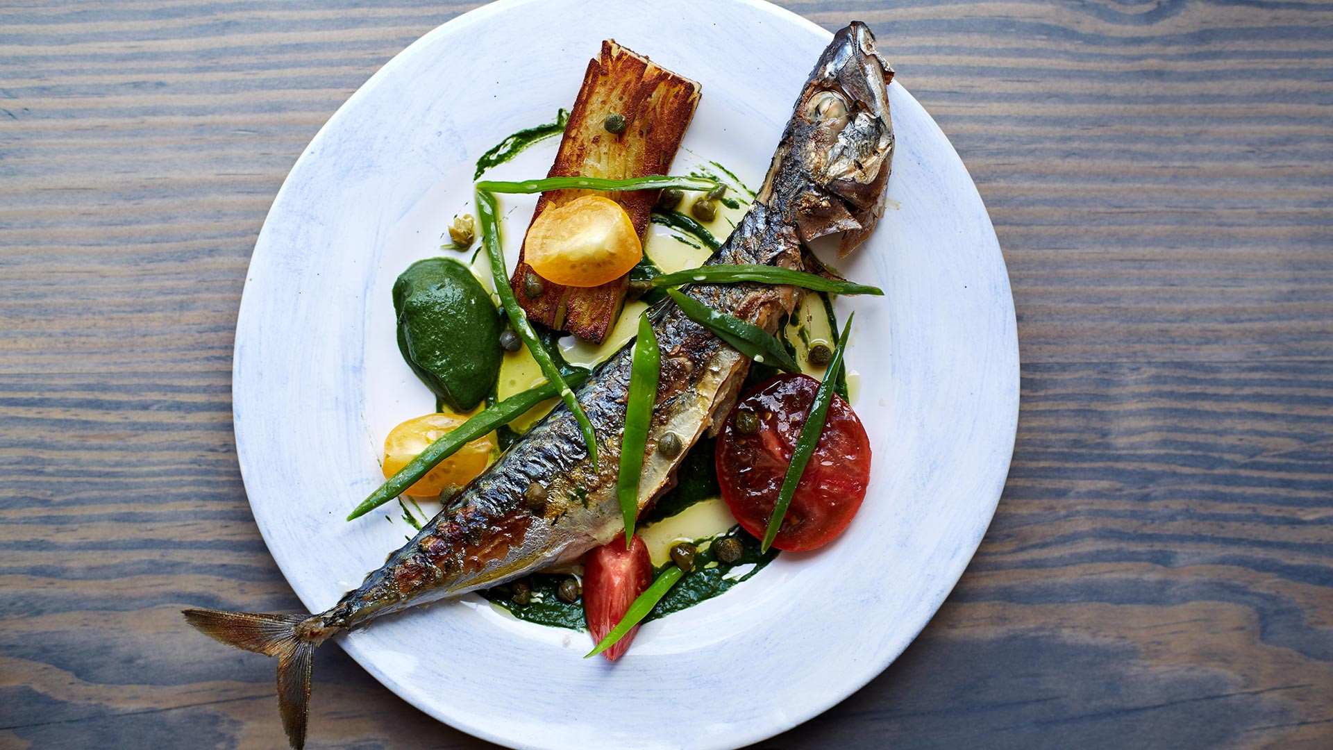 Whole mackerel with potato cakes and confit tomatoes