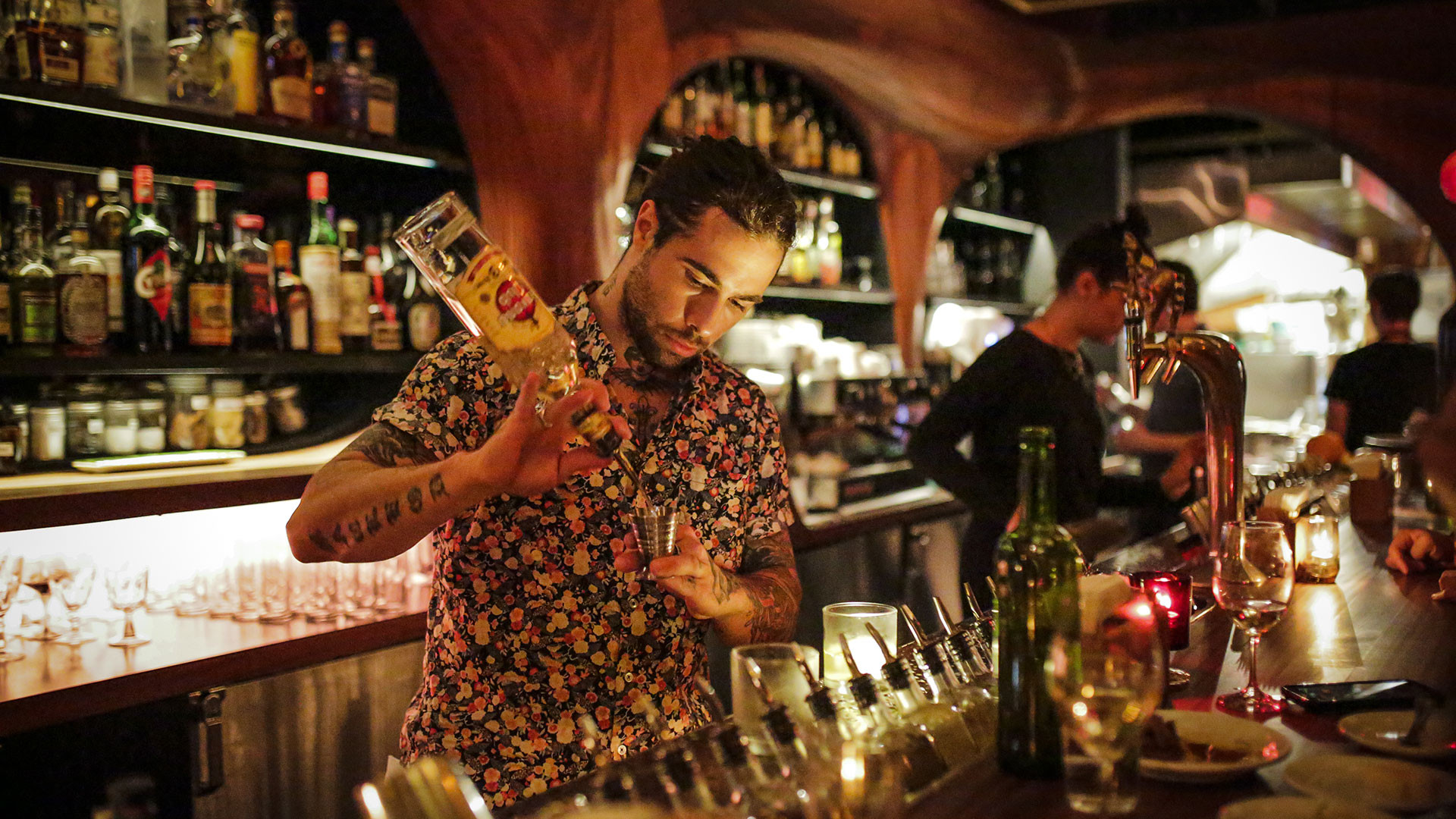 A bartender pours a drink at Bar Raval