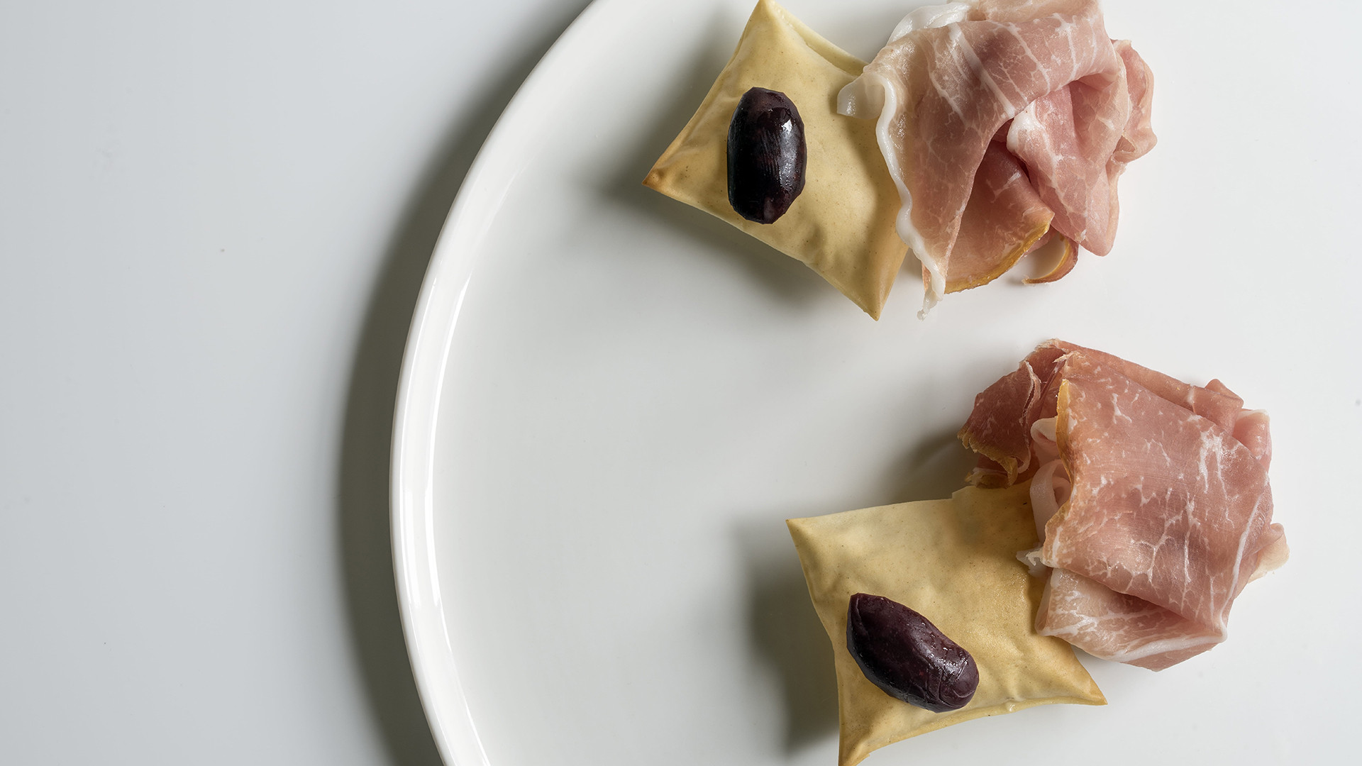 San Daniele Prosciutto, 'grissini' and Kalamata olive from Roux at the Landau