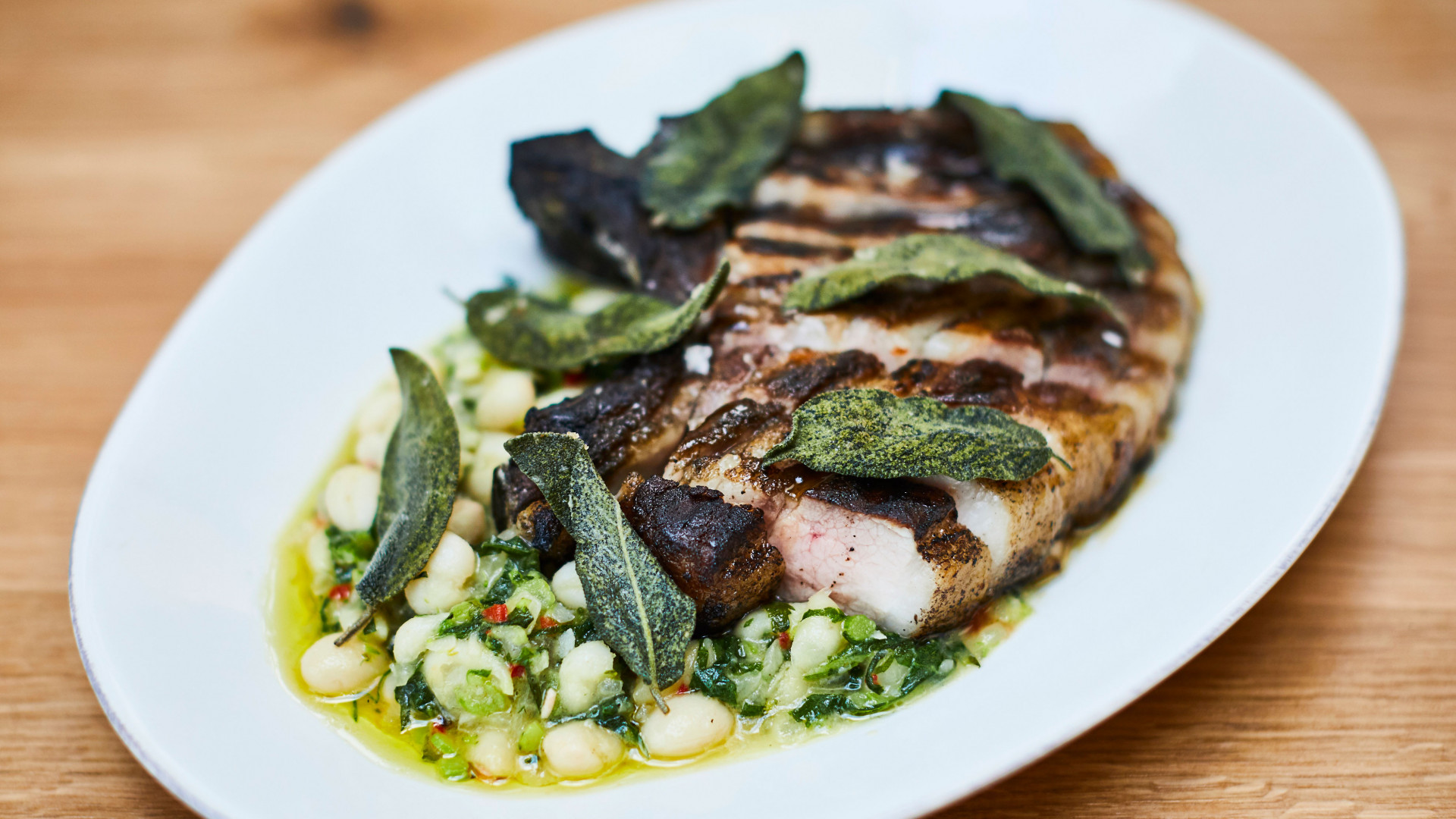 Tamworth chop with white butter beans and spring greens