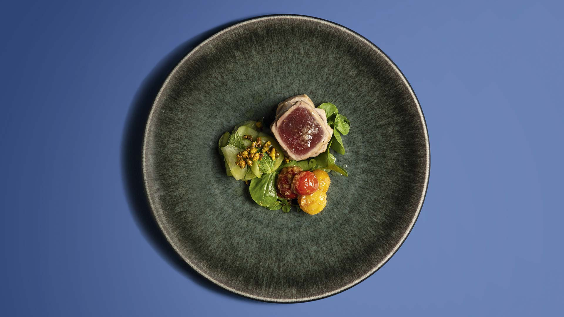 Seared tuna with tamarind roast potatoes, cucumber and pistachios