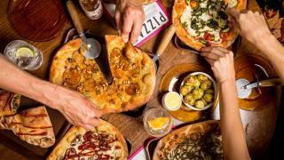 London's best pizza   people cutting into Flat Earth pizza