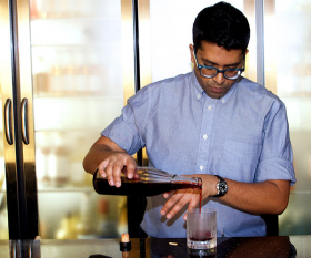 White Lyan's Chetiyawardana pouring a cocktail in his bar