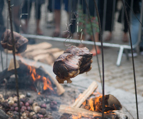 Meat cooking over a fire at Meatopia 2016