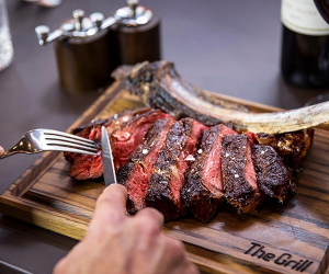 The Grill at McQueen medium rare tomahawk steak off the bone to share