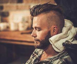 A man getting his hair cut in a distinctive skullcut style